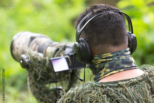 Photo  ornithologist use earphone to check signal to find bird position