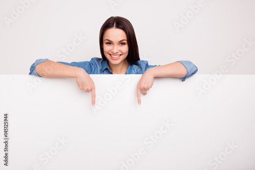 Fototapeta Cheerful cute girl is standing behind the white blank banner and pointing down at a copyspace obraz