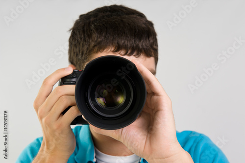 Fotografie, Tablou  Teenage boy holding up a dslr camera to take a photo isolated on gray