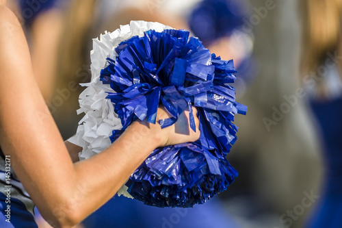 Fotomural Cheerleader holding pom poms with a shallow depth of field