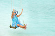 Woman enjoy on a swing above turquoise water.Copy space