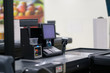 Empty cash desk with computer screen and card payment terminal on blurry background