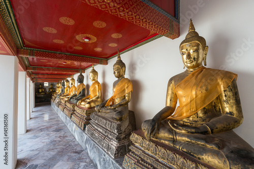 Several old statues of sitting Buddha with a cloth at the Wat Pho (Po) temple complex in Bangkok, Thailand Wallpaper Mural