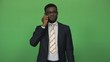 Young african businessman in formal suit answering and talking phone isolated on green background. Then turn to camera looking and smile