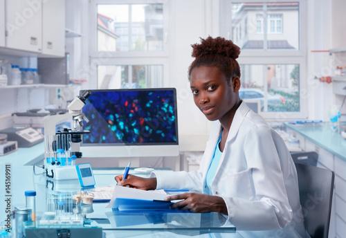 Fényképezés  Female African scientist works in modern biological laboratory