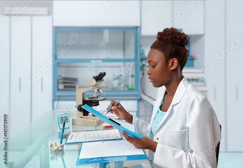 African-american biologist checks records in scientific lab or research facility Canvas Print