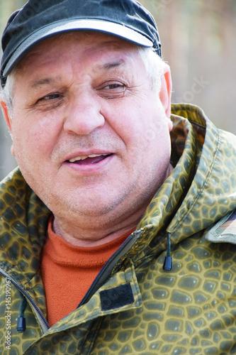 Valokuva  Senior man speaking in the forest