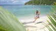 Young beautiful smiling woman is having fun on a swing at beach. Slow Motion