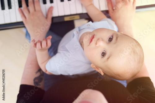 Fototapeta Baby learning to play piano with mother obraz na płótnie