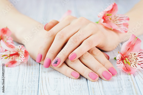 Photo sur Aluminium Manicure Woman hands with pink matted manicure on finger nails and delicate flowers