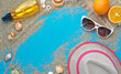 Summer background. Beach vacation accessories flat lay on sand with seashells and azure colour texture. Resort mood and relax holiday.