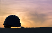 The Safety Helmet Silhouette At Construction Site With Sunset Background
