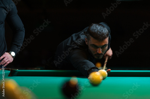 Plakat Młody człowiek bawić się bilard w zmroku klubie.