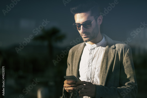 Young man looking phone behind the glass