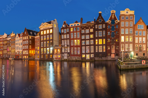 Beautiful typical Dutch dancing houses at the Amsterdam canal Damrak at night, Holland, Netherlands Wallpaper Mural