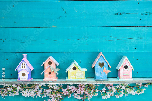 Fotografiet Row of colorful birdhouses with floral border