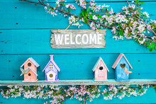 Welcome Sign Hanging Over Colorful Birdhouses And Spring Flowers
