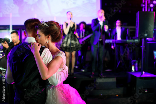 Photo Bride leans to groom tender dancing before the stage