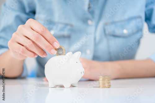 Fotografía  Woman Inserting Coin In Piggybank Showing Save Money Concept