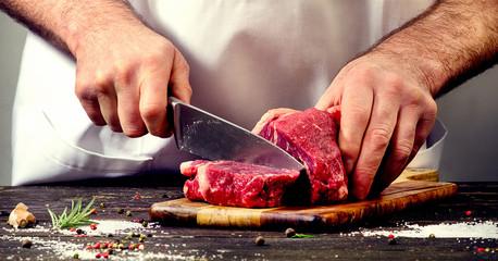 Fototapeta Man cutting beef meat