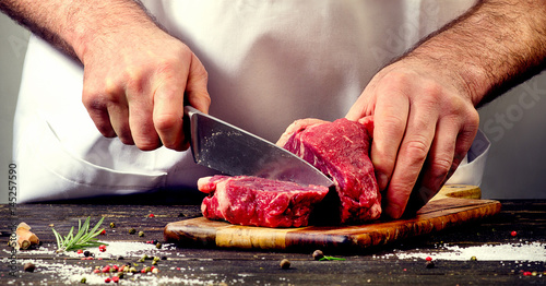 Foto op Canvas Vlees Man cutting beef meat