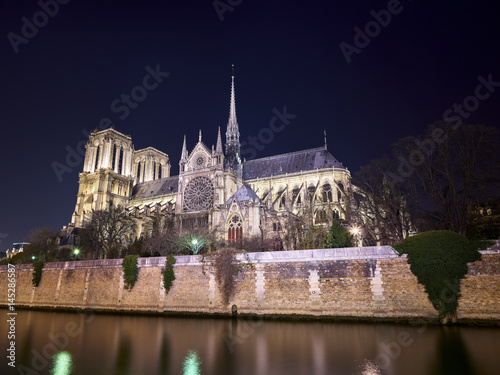 Low angle view of Notre Dame de Paris by Seine river against clear sky at night