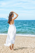 Relaxed girl in dress enjoying tropical beach. Beautiful young attractive woman in white sundress standing on beach. Clear blue water, yellow dry sand. Back view