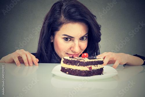 Fotografie, Obraz  Woman craving cake dessert, eager to eat sweet food