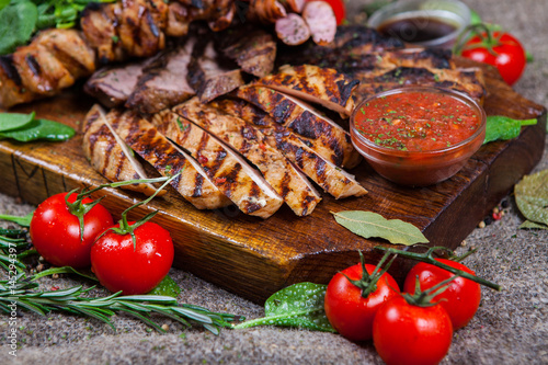 Staande foto Vlees Mixed grilled meat platter. Assorted delicious grilled meat with vegetable. Mixed grilled meat with pepper sauce and vegetables.
