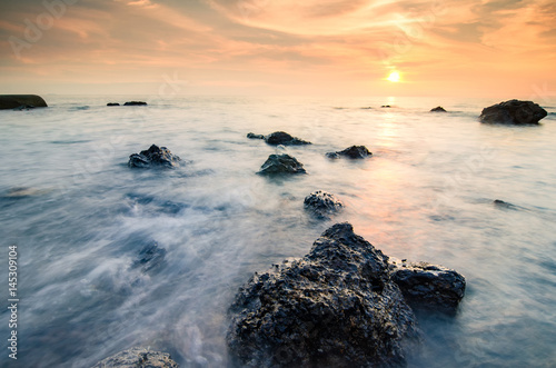 Tuinposter Koraalriffen Stunning sunset moment seascape,soft wave hitting the rock over cloudy sky. infinity focus and long exposure shot