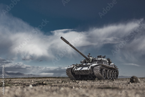 Fotografija  Military or army tank ready to attack moving over a deserted battle field terrai
