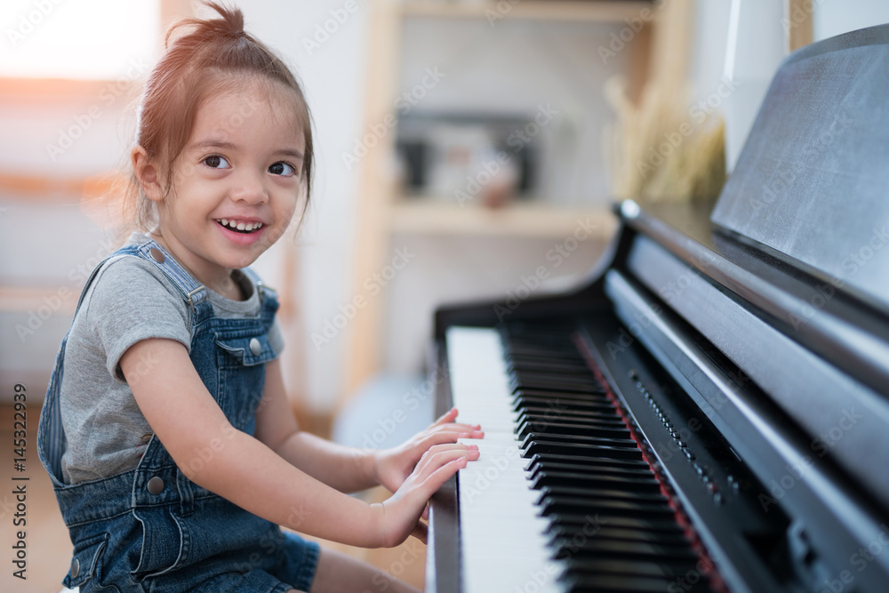 Little girl play piano and sing a song in living room <span>plik: #145322939 | autor: anekoho</span>