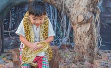 Asian Boy Hold Boa Constrictor Snake .