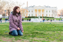 Young Woman Sitting In Grass In Park In Front Of White House At Sunset