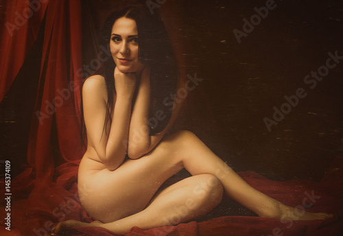 Valokuva  Naked woman sitting in colorful pieces of cloth