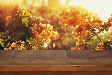 vintage wooden board table in front of summer flowers
