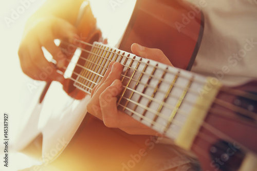 Photo Close up of young girl playing acoustic guitar