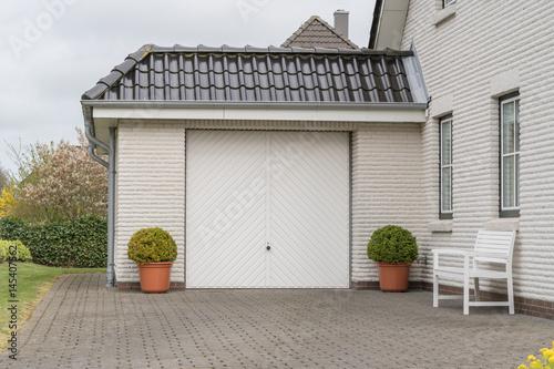 Vászonkép Garage mit Einfahrt und weißem Tor