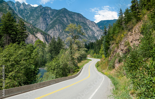 Fotografia  Scenic Road in British Columbia:  A winding tree-lined road passes a stream and rocky outcroppings in its climb through the mountains northeast of Vancouver, Canada
