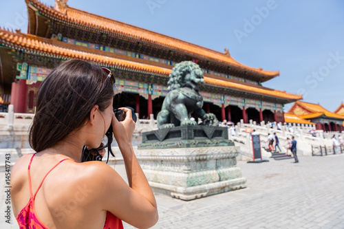 Poster Pekin Tourist photographer taking pictures with camera of sculpture in front of ancient chinese temple, china. Asia summer travel, tourism destination popular attraction
