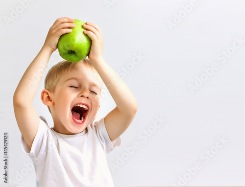Fotografía small boy holds a big green apple, healthy food and vitamins, smiling, white bac
