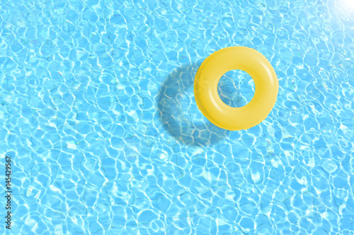Fotografija yellow swimming pool ring float in blue water