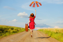 Photo Of Beautiful Young Woman With Suitcase On The Road Near Field Background