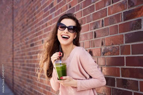 Portrait of attractive woman drinking spinach smoothie standing against brick wall