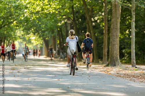 A girl and boy biking in the park. Wallpaper Mural