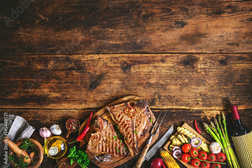 Aluminium Prints Grill / Barbecue Grilled T-bone steaks with fresh herbs, vegetables ans wine bottle