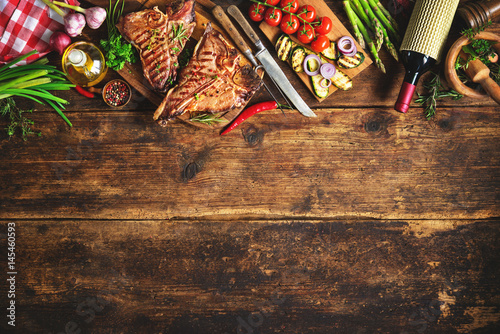 In de dag Grill / Barbecue Grilled T-bone steaks with fresh herbs, vegetables ans wine bottle