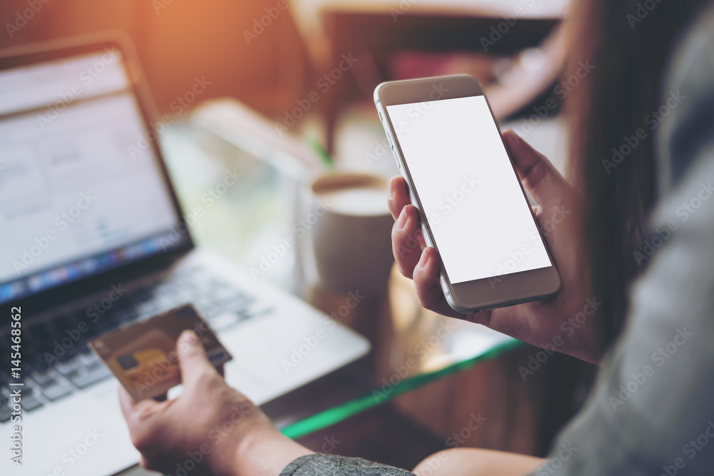 Fototapeta Mockup image of a woman holding credit card and mobile phone with blank white screen while using laptop with coffee cup on the table in office