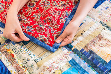 The Caucasian Female Hand Touching A Color Patchwork Quilt With Blue And Red Geometry Pattern. Part Of Colorful Scrappy Blanket Close Up. Dream Concept
