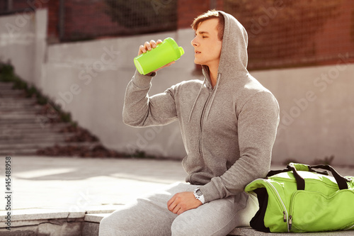Fotografia  Young active man drinking water, outdoors
